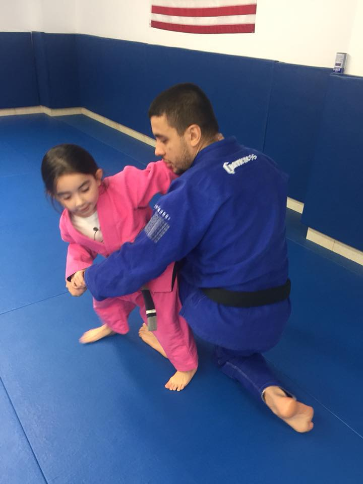 Instructor helping a young student at Lifestyle MMA