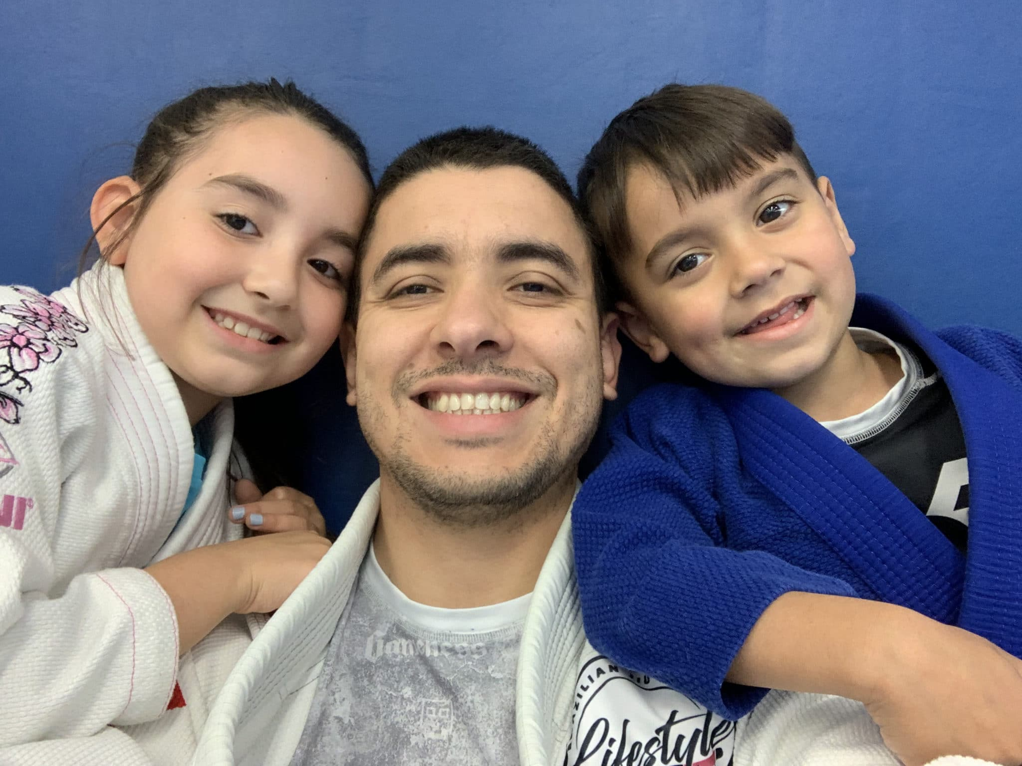 Close up of Professor Fabricio Medici and two kids at Lifestyle MMA